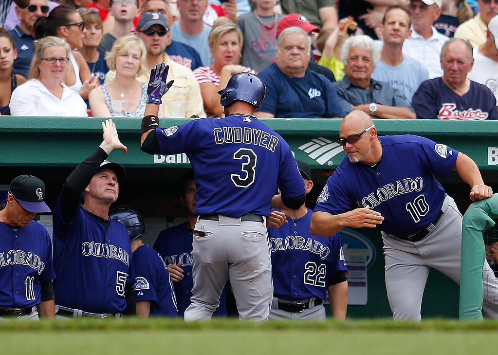 . Michael Cuddyer #3 of the Colorado Rockies celebrates with teammates after he hit the first of two home runs against the Boston Red Sox at the plate in the 6th inning at Fenway Park on June 26, 2013 in Boston, Massachusetts.  (Photo by Jim Rogash/Getty Images)