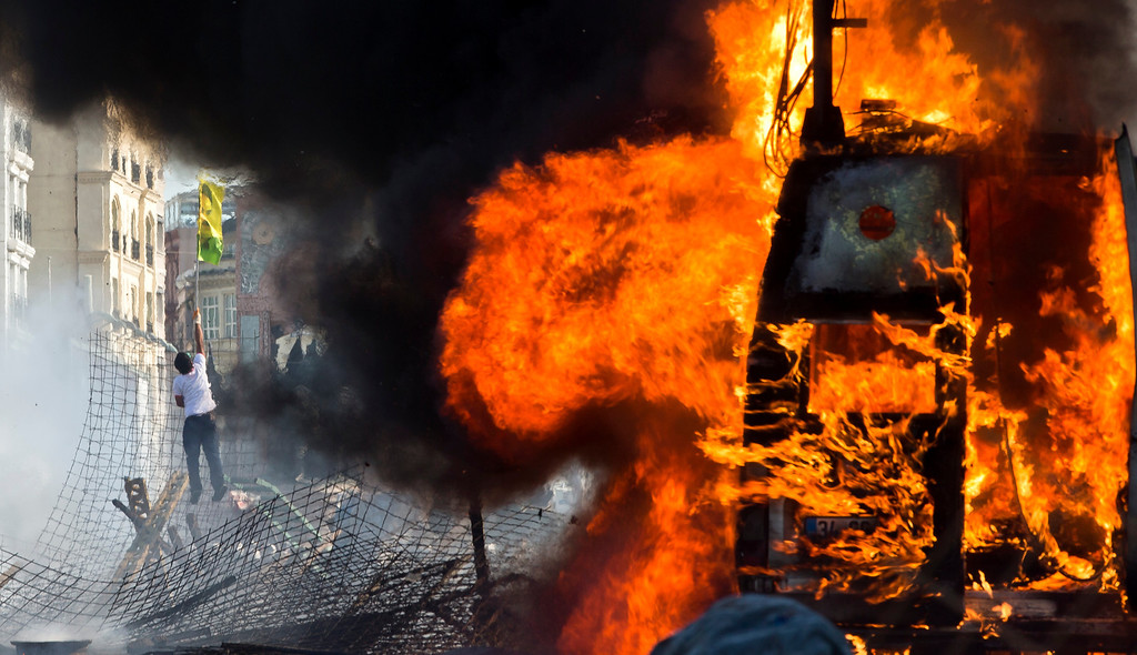 . A protester climbs a barricade waving a flag depicting jailed Kurdish rebel leader Abdullah Ocalan as a van burns during clashes at the Taksim Square in Istanbul Tuesday, June 11, 2013.  (AP Photo/Vadim Ghirda)