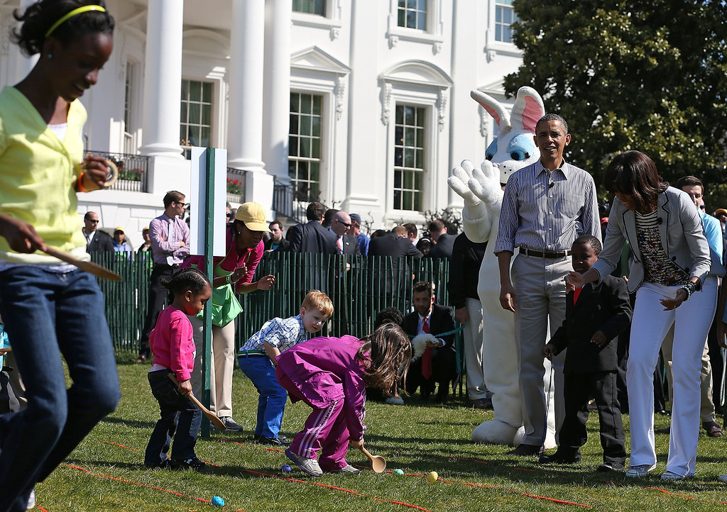 . U.S. President Barack Obama and first lady Michelle Obama watch children roll eggs during the annual Easter Egg Roll on the White House tennis court April 1, 2013 in Washington, DC. Thousands of people are expected to attend the 134-year-old tradition of rolling colored eggs down the White House lawn that was started by President Rutherford B. Hayes in 1878.  (Photo by Mark Wilson/Getty Images)