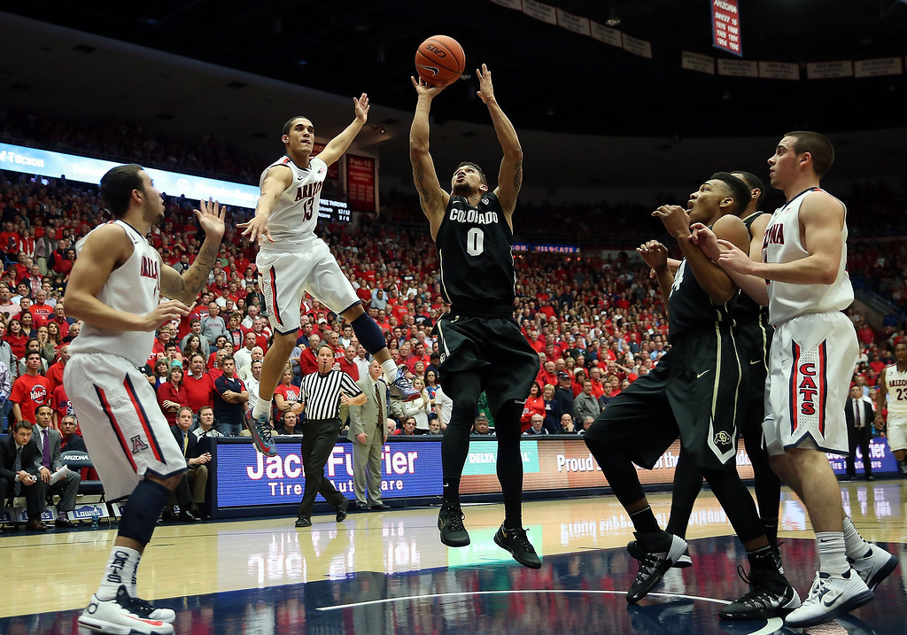 . Askia Booker #0 of the Colorado Buffaloes puts up a shot past Nick Johnson #13 of the Arizona Wildcats during the second half of the college basketball game at McKale Center on January 23, 2014 in Tucson, Arizona. The Wildcats defeated the Buffaloes 69-57.  (Photo by Christian Petersen/Getty Images)