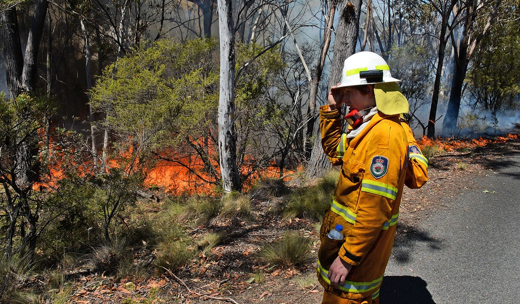 ". A firefighter monitors a back burn near Mount Victoria in the Blue Mountains on October 21, 2013, as volunteer fire brigades race to tame an enormous blaze, with officials warning it could merge with others to create a ""mega-fire\"" if weather conditions worsen.    AFP PHOTO/William  WEST/AFP/Getty Images"