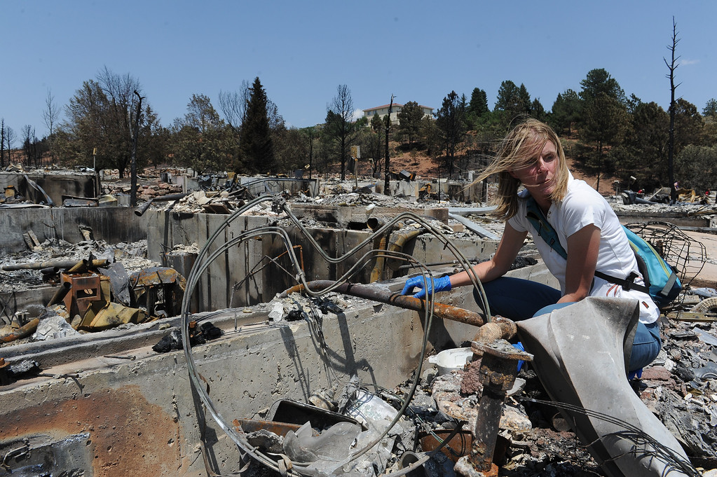 """. Chris Grove looks over her home in the Mountain Shadows neighborhood in Colorado Springs, CO, Thursday, July 05, 2012. She and her husband Michael Fender were meeting with Mark Nix and Mike Furgal, of Allstate Insurance Company to evaluate damages to their home that was destroyed by the Waldo Canyon fire on Tuesday, June 26, 2012. They have lived in the home for 13 years and paid off their mortgage a year ago. Michael said, \""""we are certain about nothing right now but... if the conditions are good we would like to rebuild bigger and better than before. The only thing potentially salvageable is the foundation... from my point of view it\'s a complete loss.\"""" Craig F. Walker, The Denver Post"""