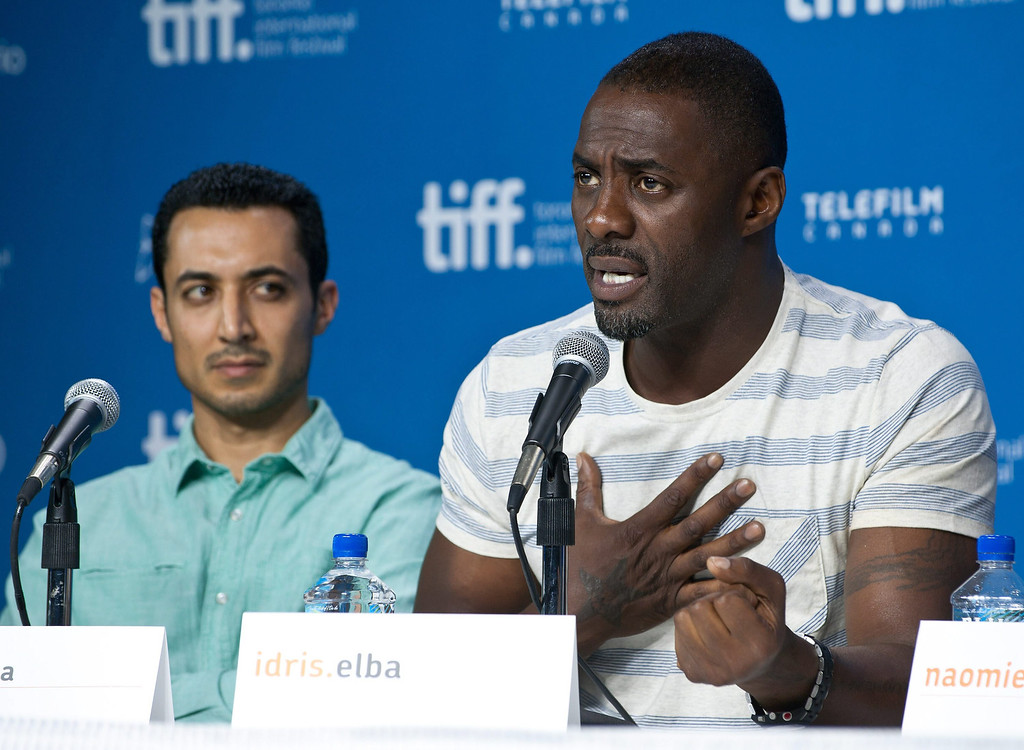 """. Actor Idris Elba (right) answers a question during the press conference for \""""Mandela: Long Walk to Freedom\"""" while actor Riaad Moosa looks on at the 2013 Toronto International Film Festival in Toronto on Sunday, Sept. 8, 2013. THE CANADIAN PRESS/Galit Rodan"""