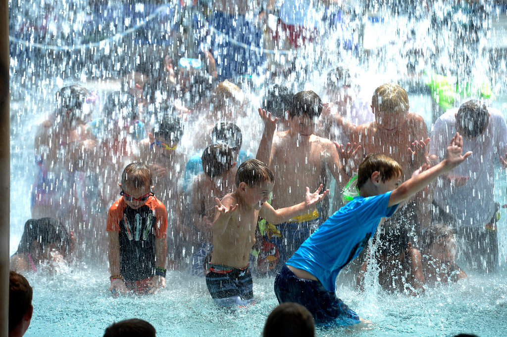. Kids stand below the big bucket as it dumps 700 gallons of water every 5 minutes at Pirates Cove July 16, 2013. (Photo By John Leyba/The Denver Post)