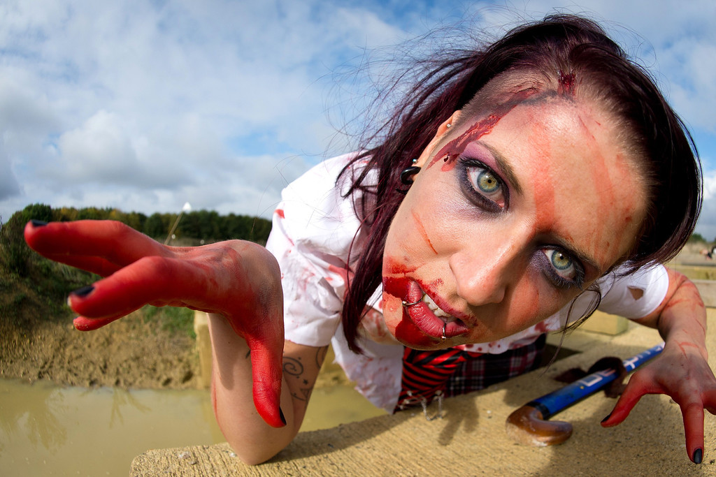 ". A zombie school girl poses for a picture as she prepares to take part in one of Britain\'s biggest horror events, the ""Zombie Evacuation Race\"" at Carver Barracks near Saffron Walden, England, on October 5, 2013. The race sees thousands of participants attempt to complete a gruelling 5 kilometre cross-country run, while evading \""zombies\"", intent on snatching the three life-line strips hanging from every runner\'s waist.  Those who manage to get through with any strips remaining are named as survivors while those without take home an \""infected\"" badge.  LEON NEAL/AFP/Getty Images"