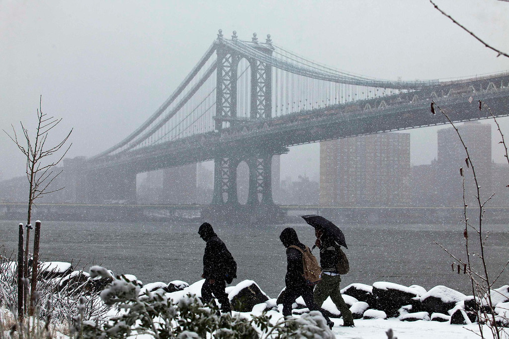 . People walk through Brooklyn Bridge Park as the skyline of New York and Manhattan bridge are seen during a snowstorm in New York March 8, 2013. REUTERS/Eduardo Munoz