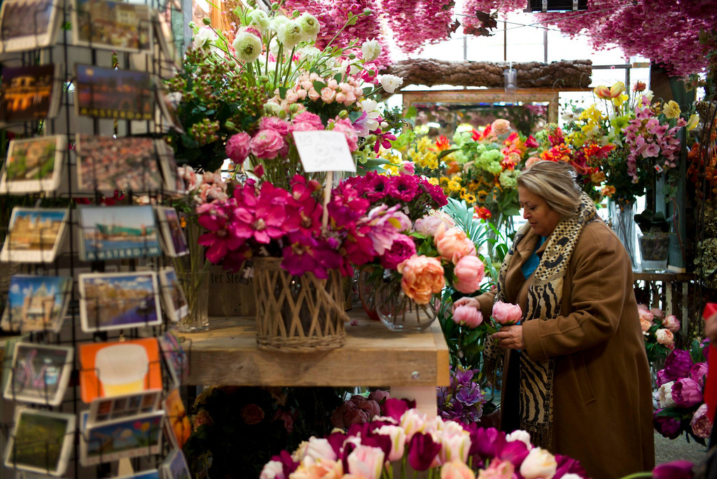 . A woman visits the floating flower market in Amsterdam, April 26, 2013. The Royal celebrations in the Netherlands this week put the country and the capital Amsterdam on front pages and television screens around the world with an orange splash. There\'s plenty to see and do in 48 hours in this compact city, where the world-famous Rijksmuseum only recently reopened after an extensive renovation. Picture taken April 26, 2013. REUTERS/Cris Toala Olivares