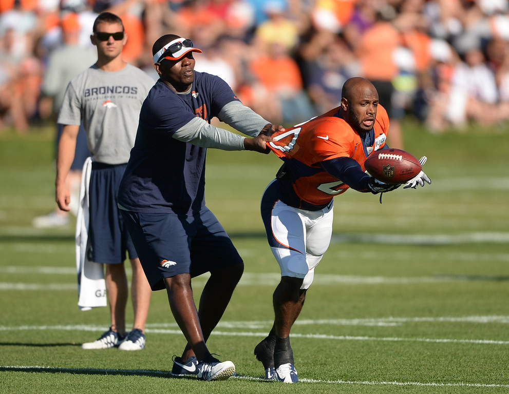 . CENTENNIAL, CO. - August 10: Sam Garnes, Assistant Secondary coach, left, and Mike Adams, Denver Broncos safety (20) run a pass defense practice during the training camp at Dove Valley. Centennial, Colorado. August 10, 2013. (Photo By Hyoung Chang/The Denver Post)