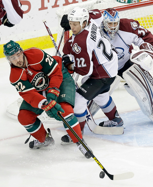 . Minnesota Wild\'s Cal Clutterbuck, left, tries to control the puck as Colorado Avalanche\'s Matt Hunwick, center, and goalie Jean-Sebastien Giguere defend in the first period of an NHL hockey game on Thursday, Feb. 14, 2013, in St. Paul, Minn. (AP Photo/Jim Mone)