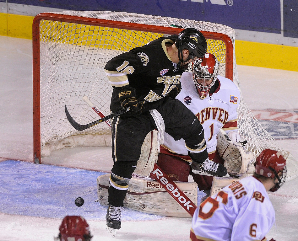 . DENVER, CO. - NOVEMBER 16: Western Michigan right wing Nolan LaPorte (16) pressured Denver goaltender Sam Brittain (1) while the puck bounced free in the crease in the final period. The University of Denver hockey team defeated Western Michigan 1-0 at Magness Arena Saturday night, November 16, 2013.  Photo By Karl Gehring/The Denver Post