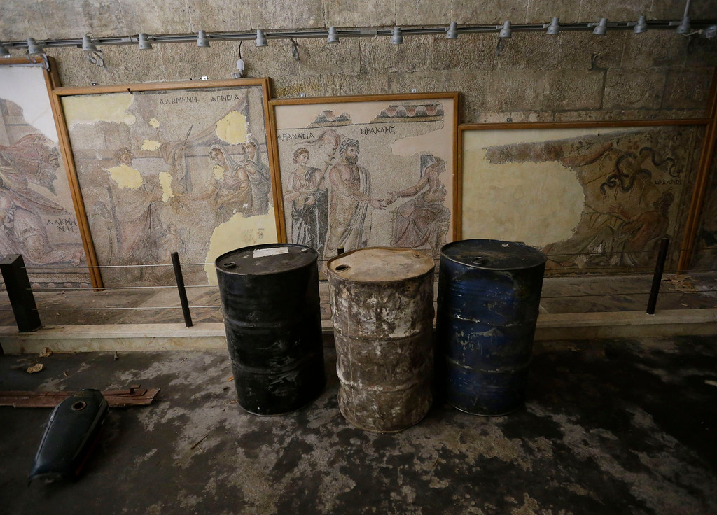 . In this photo taken Tuesday, Feb. 26, 2013, fuel barrels are stored in front of Roman and Byzantine mosaics inside the 17th-century caravanserai, which presently serves as a headquarters for the Free Syrian Army, in Maaret al-Numan, Idlib province, Syria. Across northern Syria, rebels, soldiers and civilians are making use of the country\'s wealth of ancient and medieval remains for protection. The structures are built of thick stone that has already withstood the ravages of centuries. They are often located in strategic spots overlooking towns and roads. (AP Photo/Hussein Malla)