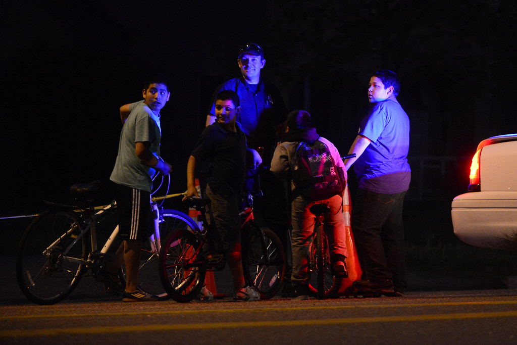 . DENVER, CO - MAY 14: Traffic officer Luke Palmatier and a group of neighborhood youths look towards the scene as police investigate the scene of an officer-involved shooting near the intersection of Harvard and Federal Boulevard. (Photo by AAron Ontiveroz/The Denver Post)