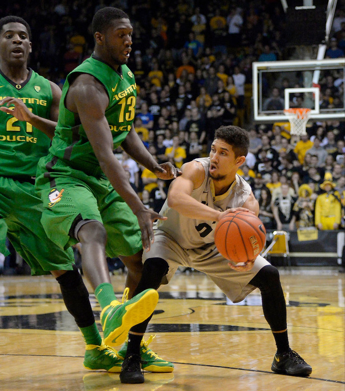 . Colorado Buffaloes guard Askia Booker (0) makes a pass around Oregon Ducks forward Richard Amardi (13) during the second half January 5, 2014 at Coors Events Center. (Photo by John Leyba/The Denver Post)