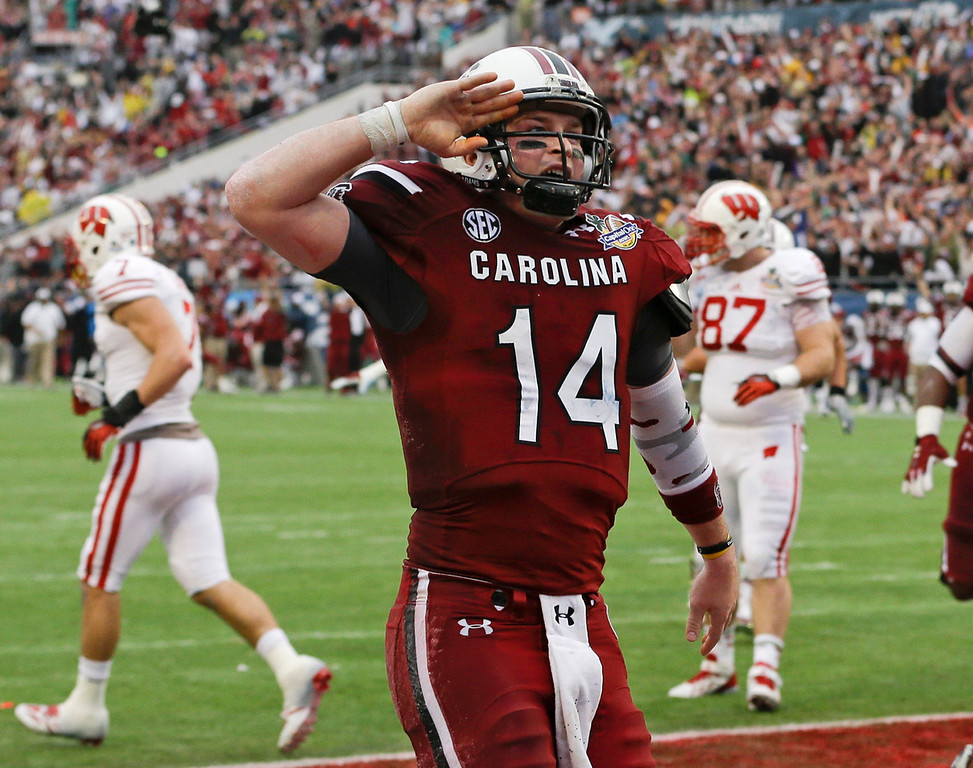 . South Carolina quarterback Connor Shaw (14) salutes towards fans after catching a touchdown on a pass from receiver Bruce Ellington during the first half of the Capital One Bowl NCAA college football game against Wisconsin in Orlando, Fla., Wednesday, Jan. 1, 2014.(AP Photo/John Raoux)
