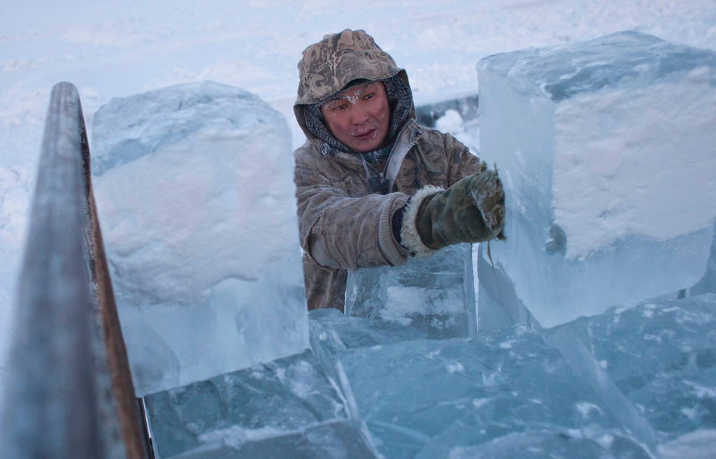 . Ruslan, 35, loads blocks of ice onto a truck outside Yakutsk in the Republic of Sakha, northeast Russia, January 17, 2013. The coldest temperatures in the northern hemisphere have been recorded in Sakha, the location of the Oymyakon valley, where according to the United Kingdom Met Office a temperature of -67.8 degrees Celsius (-90 degrees Fahrenheit) was registered in 1933 - the coldest on record in the northern hemisphere since the beginning of the 20th century. Yet despite the harsh climate, people live in the valley, and the area is equipped with schools, a post office, a bank, and even an airport runway (albeit open only in the summer).    Picture taken January 17, 2013.    REUTERS/Maxim Shemetov