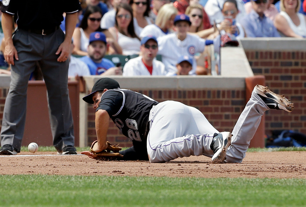 . Colorado Rockies third baseman Nolan Arenado (28) can\' t make the play on a single hit by Chicago Cubs\' Arismendy Alcantara during the sixth inning of a baseball game in Chicago, Thursday, July 31, 2014. (AP Photo/Nam Y. Huh)