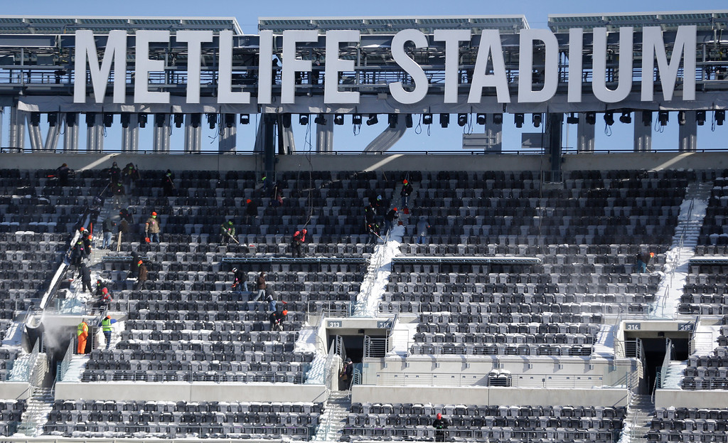 . Workers shovel snow off the seats at MetLife Stadium as crews removed snow ahead of Super Bowl XLVIII following a snow storm, Wednesday, Jan. 22, 2014, in East Rutherford, N.J.  (AP Photo/Julio Cortez)