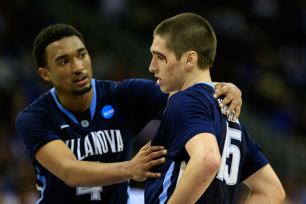 . KANSAS CITY, MO - MARCH 22:  Darrun Hilliard #4 of the Villanova Wildcats helps his teammate Ryan Arcidiacono #15 after he was injured in the second half against the North Carolina Tar Heels during the second round of the 2013 NCAA Men\'s Basketball Tournament at the Sprint Center on March 22, 2013 in Kansas City, Missouri. North Carolina won 78-71. (Photo by Jamie Squire/Getty Images)