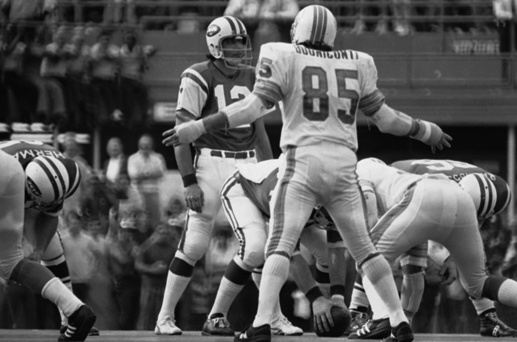. Miami middle line backer Nick Buoniconti (85) has his arms extended as he heckles New York Jets quarterback Joe Namath (12) during the final period in game, Sunday, Nov. 20, 1972 in the Orange Bowl in Miami, Florida. Namath was calling for quiet in the stadium to start a play and Nick was hollering at him. The Dolphins downed the Jets, 28-24 to post their 10th win of the season against no losses. (AP Photo/Steve Starr)