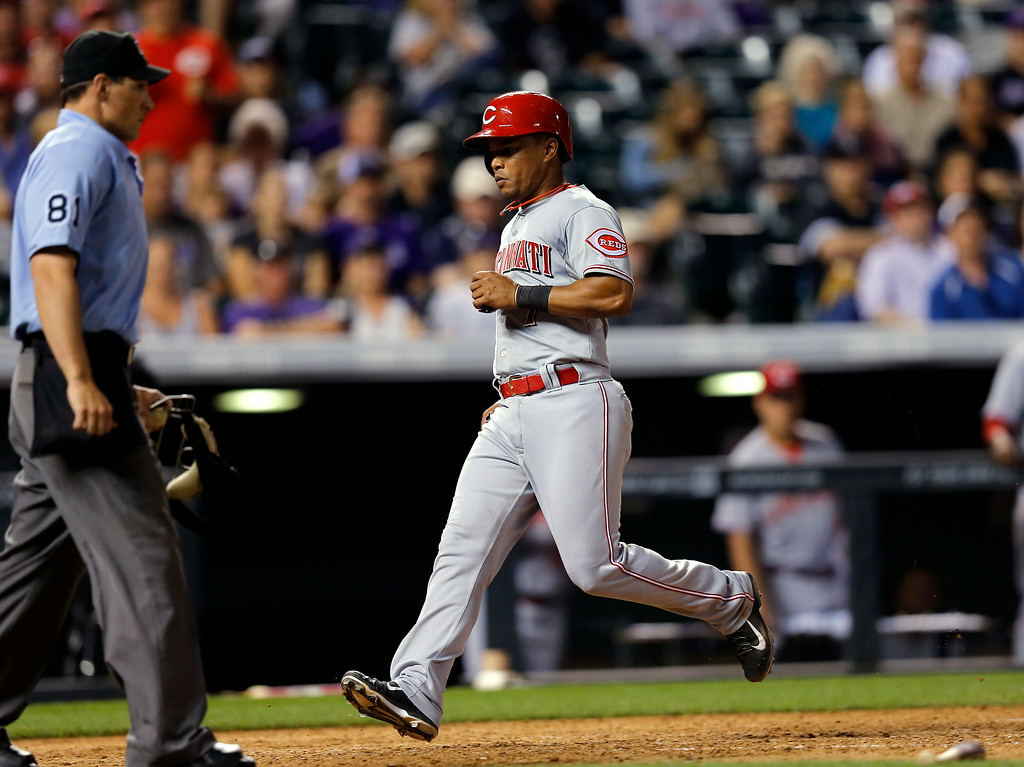 . Cincinnati Reds\' Ramon Santiago scores against the Colorado Rockies during the ninth inning of a baseball game Friday, Aug. 15, 2014, in Denver. (AP Photo/Jack Dempsey)