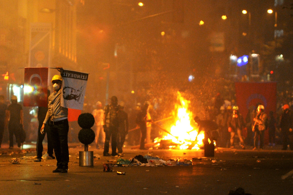 """. An anti-goverment protestor wawes a Turk\'sih flag and Mustafa Kemal Ataturk\""""s poster , founder of modern Turkey at Harbiye near Taksim square in Istanbul, on June 16, 2013. Police fired tear gas and jets of water to disperse hundreds of demonstrators in Istanbul\'s Taksim Square, shortly after Turkish Prime Minister Recep Tayyip Erdogan warned police would intervene to end protesters\' occupation of a park bordering the square. Turkish protesters today had refused to budge from an Istanbul park at the centre of nationwide anti-government demonstrations after rejecting a government olive branch aimed at ending two weeks of deadly unrest.     AFP PHOTO/OZAN KOSEOZAN KOSE/AFP/Getty Images"""