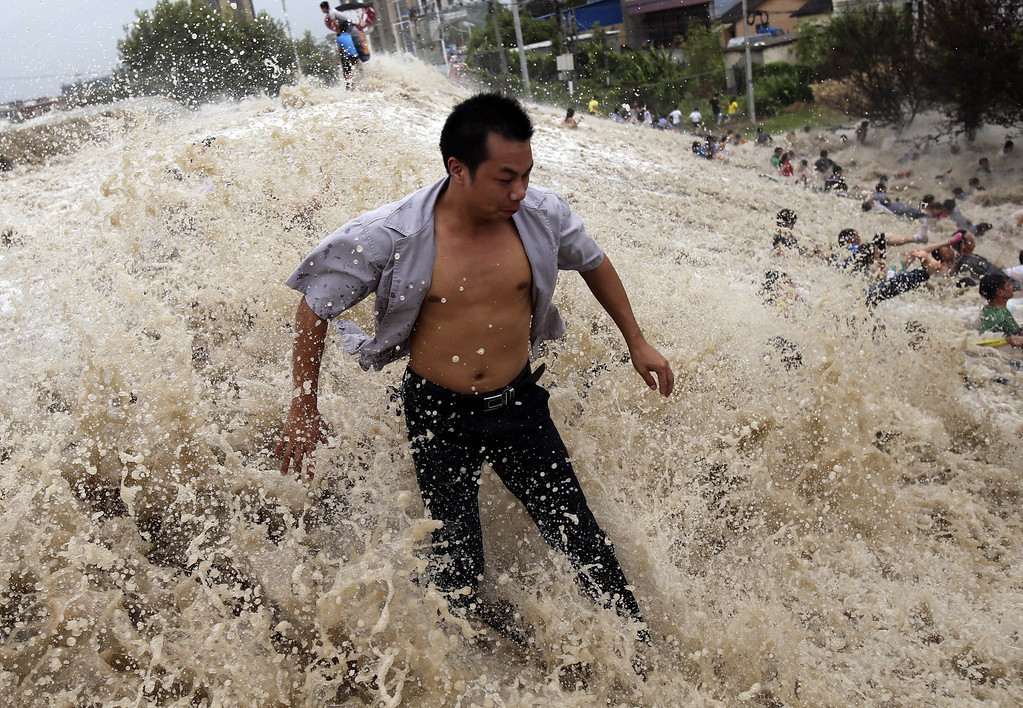 ". This picture taken on August 22, 2013 shows onlookers (R) being washed away from huge waves from the ""Haining tide\"" - a daily occurrence when the river tides hit the banks of the city - as the waves surged higher than usual due to the influence of Typhoon Trami in the region in Haining, in eastern China\'s Zhejiang province. State media reported on August 23 that 30 people were injured and 11 still in hospital after the wave hit.  Typhoon Trami, the 12th typhoon to hit China this year, brought rainstorms and wreaked havoc in eastern China after landing in Fujian Province early on August 22.         AFP PHOTOSTR/AFP/Getty Images"
