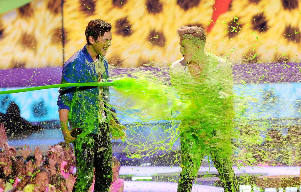 . Singers Austin Mahone (L) and Cody Simpson get slimed onstage during Nickelodeon\'s 27th Annual Kids\' Choice Awards held at USC Galen Center on March 29, 2014 in Los Angeles, California.  (Photo by Kevin Winter/Getty Images)