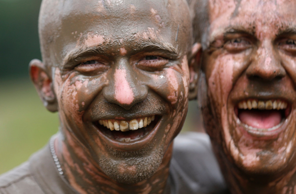 """. Participants of the \""""Tough Mudder\"""" endurance event series runs are seen with mud-covered faces after clearing the \""""Mud Mile\"""" obstacle in the Fursten Forest, a former British Army training ground near the north-western German city of Osnabrueck July 13, 2013. The hardcore but un-timed event over 16 km (10 miles) was designed by British Special Forces to test mental as well as physical strength. Some 4,000 competitors had to overcome obstacles of common human fears, such as fire, water, and heights.   REUTERS/Wolfgang Rattay"""
