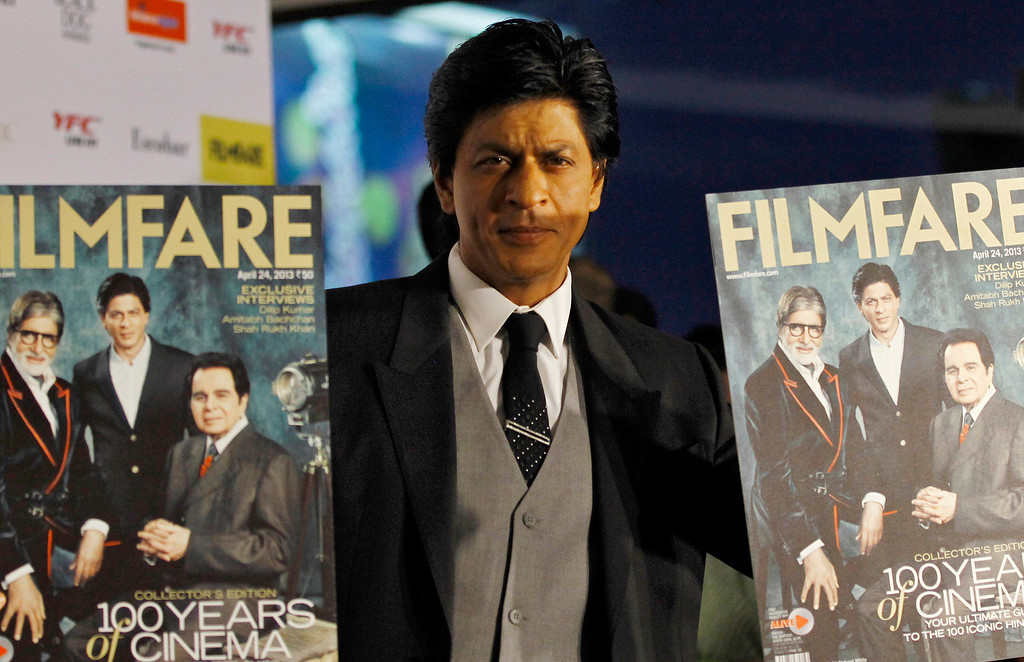 . In this Wednesday, April 10, 2013 photo, Bollywood star Shahrukh Khan poses for photographers with copies of the Filmfare magazine after unveiling it to celebrate 100 years of Indian cinema, at an event in Mumbai, India. (AP Photo/Rafiq Maqbool)