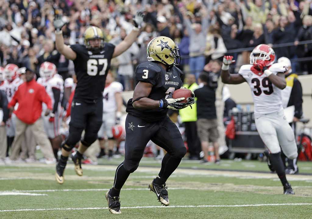 . Vanderbilt running back Jerron Seymour (3) scores the game-winning touchdown on a 13-yard run in the fourth quarter of an NCAA college football game on Saturday, Oct. 19, 2013, in Nashville, Tenn. Behind Seymour are Vanderbilt offensive linesman Wesley Johnson (67) and Georgia safety Corey Moore (39). Vanderbilt upset No. 15 Georgia 31-27. (AP Photo/Mark Humphrey)