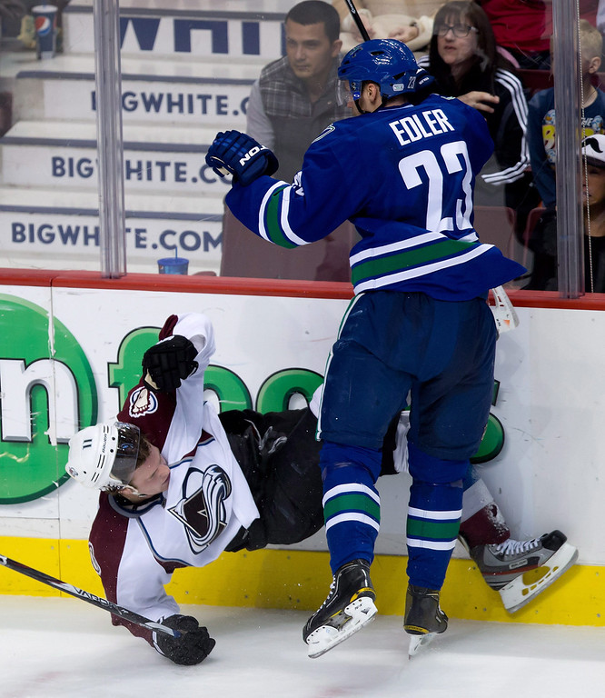 . Vancouver Canucks\' Alexander Edler, right, of Sweden, checks Colorado Avalanche\'s Jamie McGinn to the ice during the second period of an NHL hockey game in Vancouver, British Columbia, on Thursday, March 28, 2013. (AP Photo/The Canadian Press, Darryl Dyck)