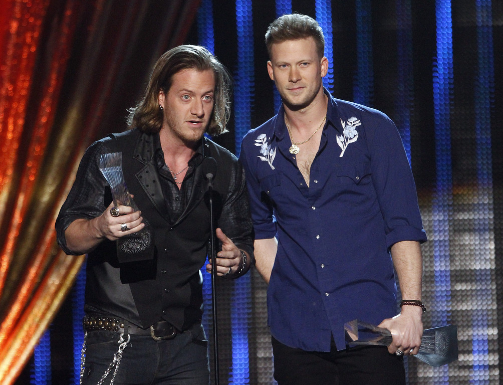 """. Tyler Hubbard, left, and Brian Kelley of Florida Georgia Line accept their award at CMT \""""Artists of the Year\"""" show held at the Music City Center on Tuesday, Dec. 3, 2013, in Nashville, Tenn. (Photo by Wade Payne/Invision/AP)"""