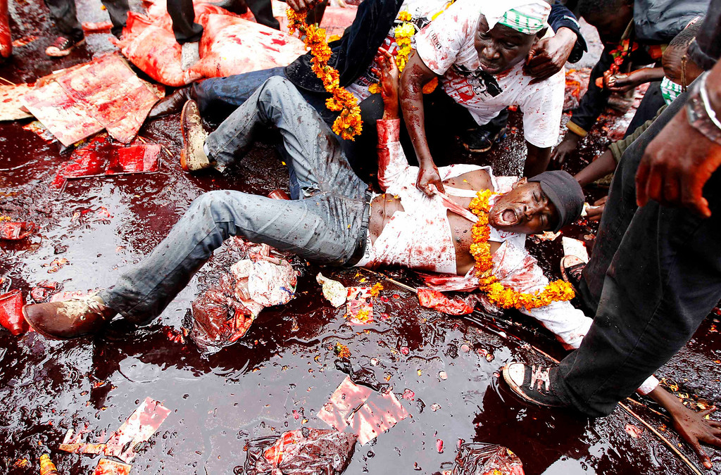 . A protester lies in animal blood as he participates in a demonstration against lawmakers\' demands for a pay rise, outside parliament buildings in Nairobi, June 11, 2013. Refusing to accept a cut imposed by the Salaries and Remuneration Commission in May, members of parliament voted to increase their salaries to 130 times the minimum wage, which according to them, are needed to deter bribery and provide charitable support for constituents. Protesters have deemed the proposed salary raise a violation of the constitution, according to news reports. REUTERS/Thomas Mukoya