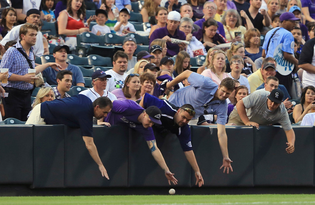 . Fans attempt to retrieve a foul ball on the leftfield line as the Washington Nationals face the Colorado Rockies at Coors Field on June 12, 2013 in Denver, Colorado.  (Photo by Doug Pensinger/Getty Images)