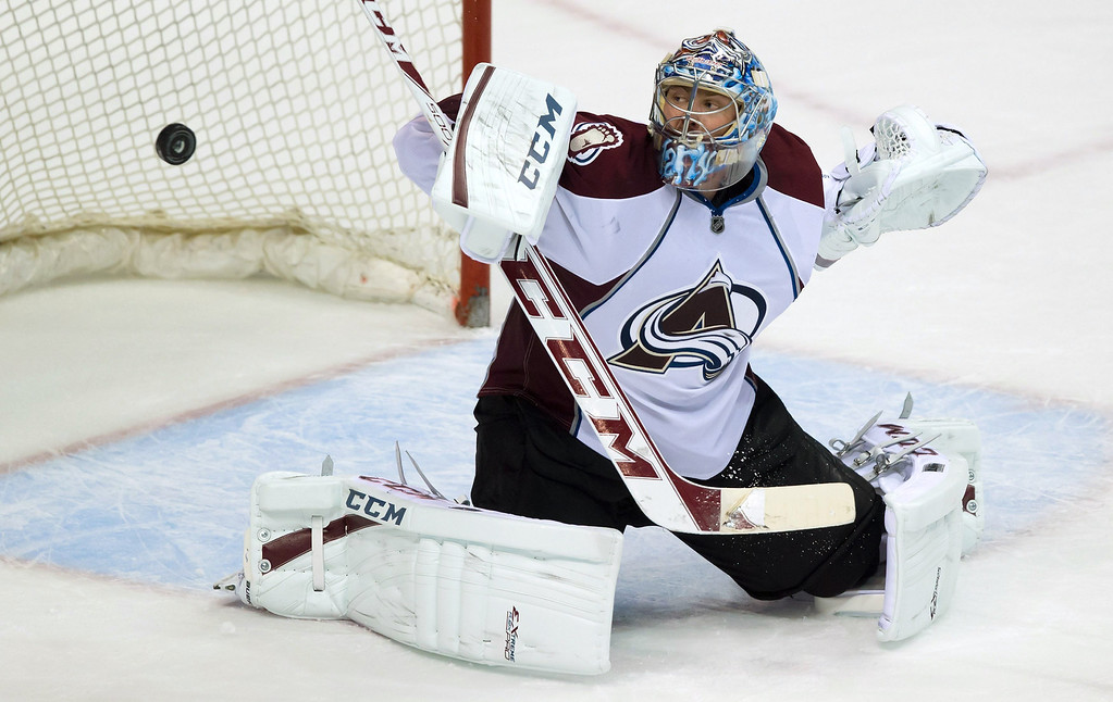 . Colorado Avalanche goalie Semyon Varlamov, of Russia, makes a blocker save against the Vancouver Canucks during the third period of an NHL hockey game Thursday, April 10, 2014, in Vancouver, British Columbia. (AP Photo/The Canadian Press, Darryl Dyck)