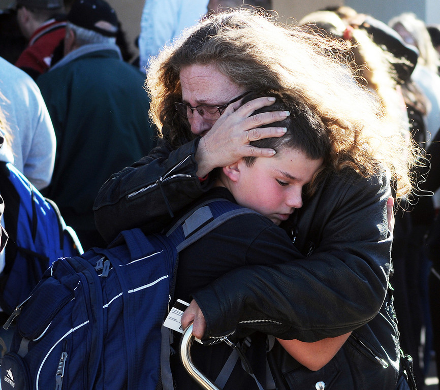 . A woman hugs a student at a staging ground set up at the Roswell Mall following a shooting at Berrendo Middle School, Tuesday, Jan. 14, 2014, in Roswell, N.M. A shooter opened fire at the middle school, injuring at least two students before being taken into custody. Roswell police said the school was placed on lockdown, and the suspected shooter was arrested. (AP Photo/Roswell Daily Record, Mark Wilson)