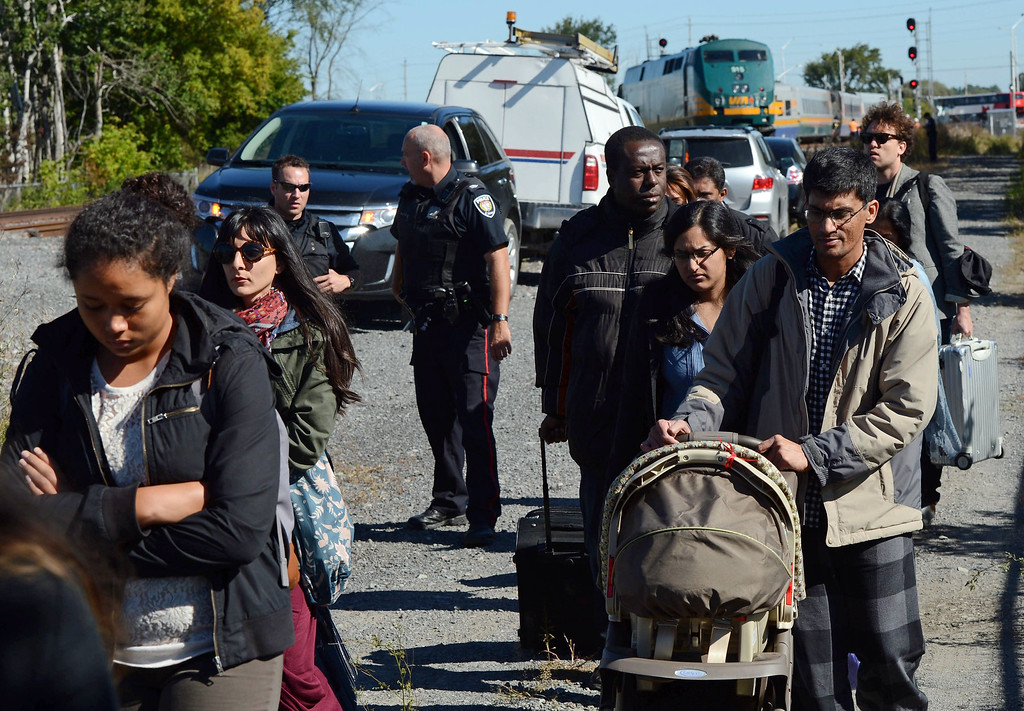 . Train passengers are escorted away from the scene following a collision with a city bus in Ottawa, Ontario, Wednesday, Sept. 18, 2013. An Ottawa Fire spokesman said there are ìmultiple fatalitiesî and a number of people injured from the bus, but no injuries reported from the train. (AP Photo/The Canadian Press, Sean Kilpatrick)