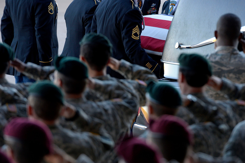 . Green Beret and Airborne salute as military officials load the casket on to the hearse as military officials brought the body of special forces staff sergeant Liam Nevins, 32, home from Dover AFB September 30, 2013 at Buckley AFB. Nevins, of Denver, was killed two weekends ago in Afghanistan. (Photo by John Leyba/The Denver Post)
