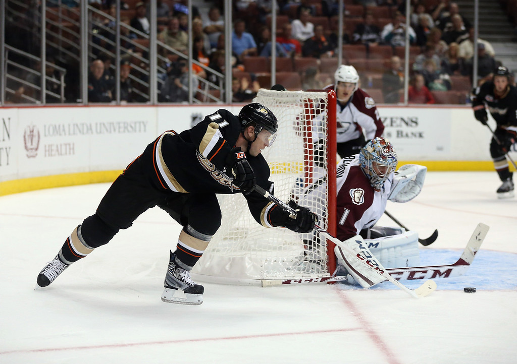. Saku Koivu #11 of the Anaheim Ducks skates around the net and shoots on goaltender Semyon Varlamov #1 of the Colorado Avalanche in the third period at Honda Center on September 22, 2013 in Anaheim, California. The Avalanche defeated the Ducks 2-1.  (Photo by Jeff Gross/Getty Images)