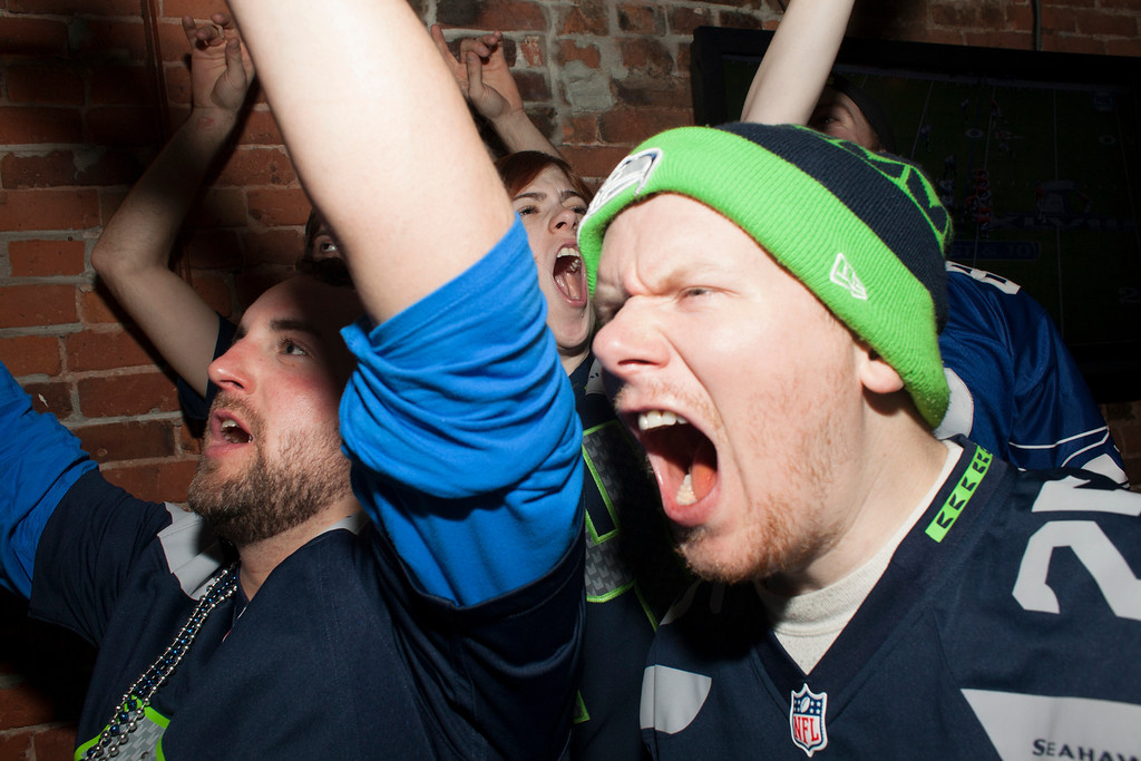 . Seattle Seahawks fans cheer while watching the Super Bowl at Fuel, a bar on February 2, 2014 in Seattle, Washington. The Seahawks defeated the Denver Broncos 43-8 in Super Bowl XLVIII.  (Photo by David Ryder/Getty Images)