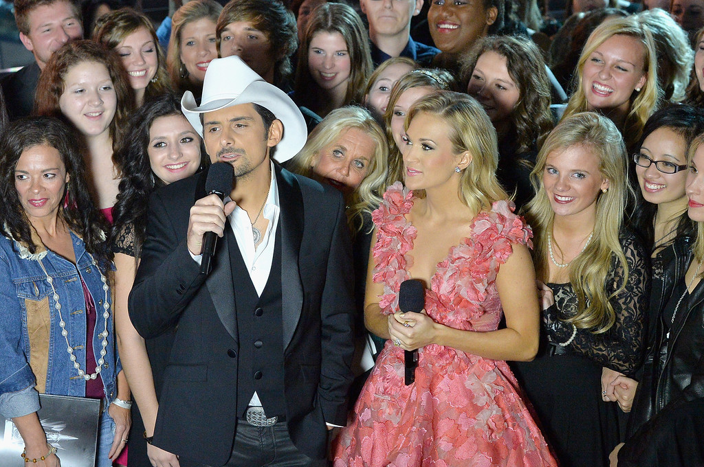 . NASHVILLE, TN - NOVEMBER 06:  Hosts Brad Paisley (L) and Carrie Underwood speak during the 47th annual CMA Awards at the Bridgestone Arena on November 6, 2013 in Nashville, Tennessee.  (Photo by Rick Diamond/Getty Images)
