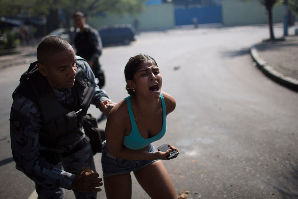 . A woman screams while being detained during protests near the area recently occupied by squatters in Rio de Janeiro, Brazil, Friday, April 11, 2014. The woman was later released. Squatters in Rio de Janeiro are clashing with police after a Brazilian court ordered that 5,000 people be evicted from abandoned buildings of a telecommunications company. Officers have used tear gas and stun grenades to try to disperse the families. (AP Photo/Felipe Dana)