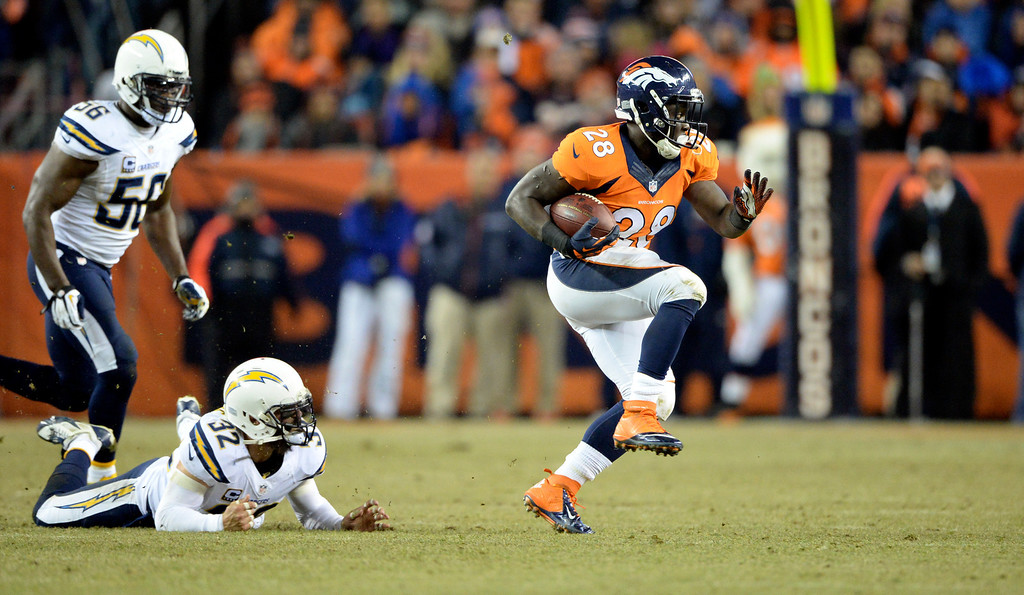 . Denver Broncos running back Montee Ball (28) gains some yards against San Diego Chargers free safety Eric Weddle (32) and San Diego Chargers inside linebacker Donald Butler (56) during the second half.  The Denver Broncos vs. the San Diego Chargers at Sports Authority Field at Mile High in Denver on December 12, 2013. (Photo by Hyoung Chang/The Denver Post)