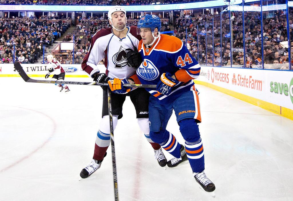 . Colorado Avalanche\'s Patrick Bordeleau (58) checks Edmonton Oilers\' Corey Potter (44) during first-period NHL hockey game action in Edmonton, Alberta, Thursday, Dec. 5, 2013. (AP Photo/The Canadian Press, Jason Franson)