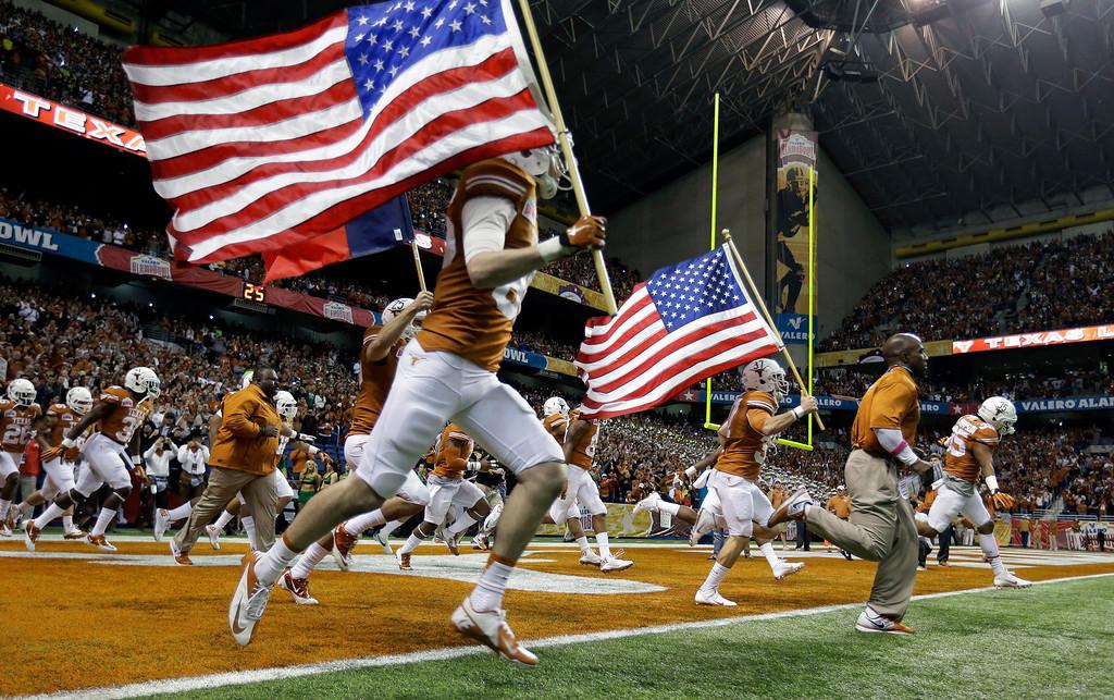 . Texas players run onto the field for the Valero Alamo Bowl NCAA college football game against Oregon, Monday, Dec. 30, 2013, in San Antonio. (AP Photo/Eric Gay)