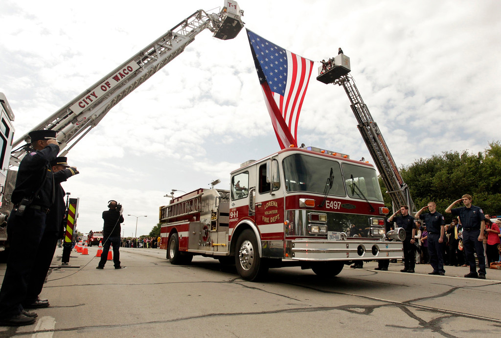 . Firefighters salute as a procession of fire trucks and emergency vehicles pass under a flag before a memorial service for the victims of the West, Texas fertilizer plant explosion last week, at Baylor University in Waco, Texas, April 25, 2013.  REUTERS/Richard Rodriguez