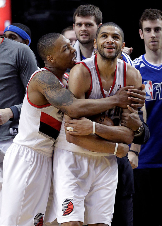 . Portland Trail Blazers guard Damian Lillard, left, hugs teammate Nicolas Batum after winning an NBA basketball game against the Los Angeles Clippers in Portland, Ore., Saturday, Jan. 26, 2013.  Both players scored 20 points each as the Trail Blazers won 101-100. (AP Photo/Don Ryan)