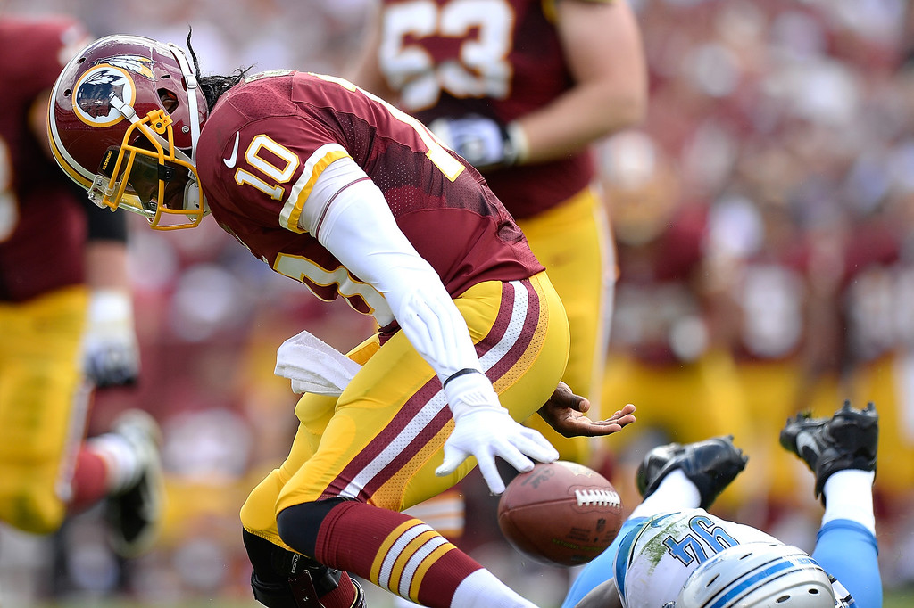 . LANDOVER, MD - SEPTEMBER 22:  Robert Griffin III #10 of the Washington Redskins fumbles and recovers the ball after being sacked in the second quarter during a game against the Detroit Lions at FedExField on September 22, 2013 in Landover, Maryland.  (Photo by Patrick McDermott/Getty Images)