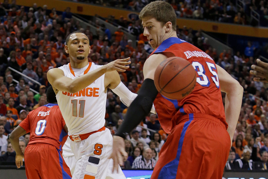 . Syracuse\'s Tyler Ennis (11) passes the ball behind Dayton\'s Matt Kavanaugh (35) during the first half of a third-round game in the NCAA men\'s college basketball tournament in Buffalo, N.Y., Saturday, March 22, 2014. (AP Photo/Nick LoVerde)