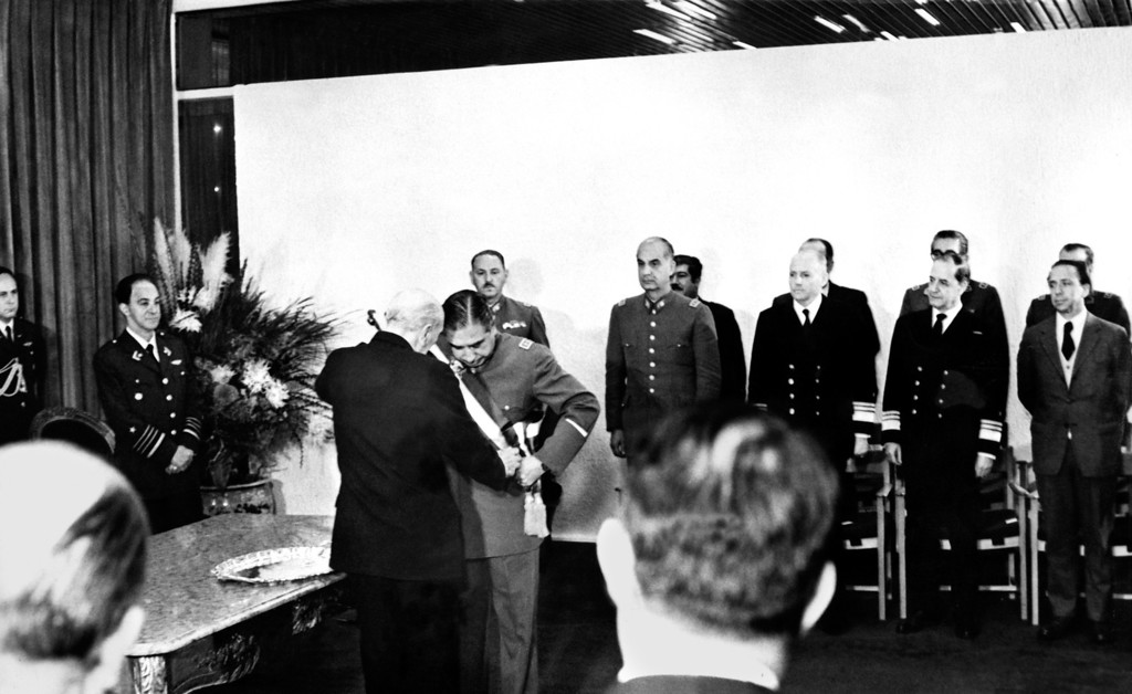 . Chile\'s Supreme Court of Justice president (L) gives the presidential sash to General Augusto Pinochet who becomes Chile\'s supreme chief, in September 1973. The military coup d\'etat led by Augusto Pinochet against the constitutional President Salvador Allende, took place in Santiago 11 September 1973. President Allende died on 11 September 1973 and Augusto Pinochet established himself as the head of the ensuing military regime.-/AFP/Getty Images